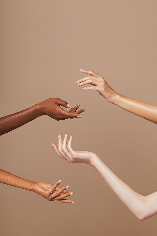 Vier Arme präsentieren lackierte Nägel