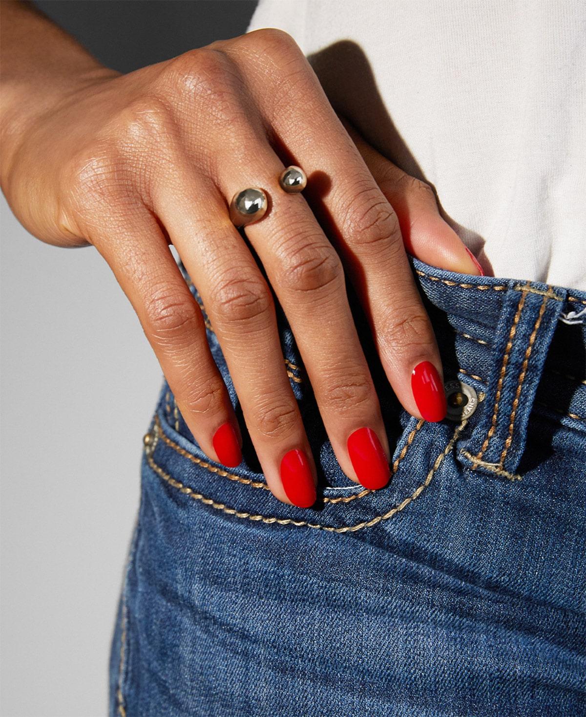 Lackierte Nägel an Jeans